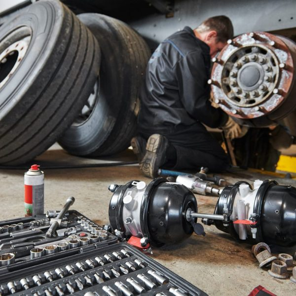 Truck repair service. Mechanic works with brakes in truck worksh